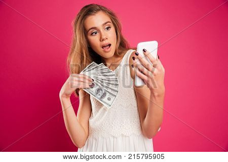 Portrait of a shocked pretty girl holding money banknotes while resding message on mobile phone isolated over pink background