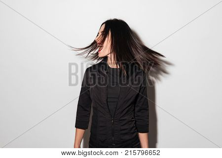 Portrait of a happy woman spinning her head isolated over white background