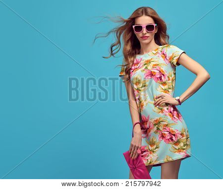 Fashion Young woman in Floral Dress. Trendy wavy Hairstyle. Glamour Sexy Blond Model in fashion pose, Stylish Sunglasses, fashion Clutch. Playful Summer Girl on Blue