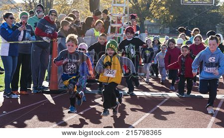 West Islip NY USA - 24 November 2017: The start of the kids fun run on a red track with their parents cheering them on at a local turkey trot race on Thanksgiving weekend.