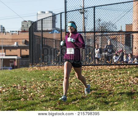 West islip NY USA - 24 November 2017: The first female runner exiting the road over some grass on her way to the track and the final 400 meters.
