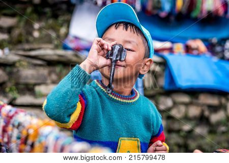 Annapurna track, Nepal - 08 October 2017: Portrait of smilling Nepalese boy who holds small elephant statue against his nose, Annapurna track, Himalayas.