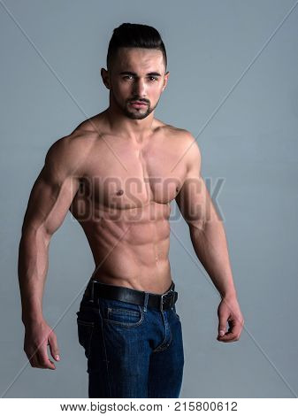 Man with muscular body and torso. Coach sportsman with bare chest in jeans. Athletic bodybuilder man on grey background. Sport and workout. Dieting and fitness.