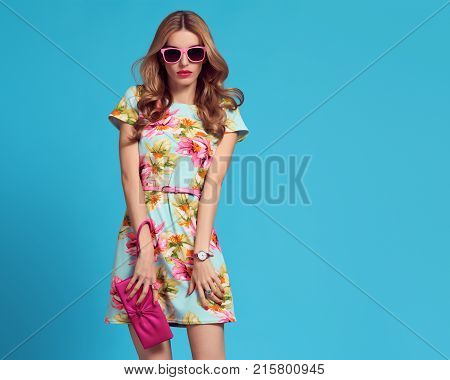 Fashion. Glamour Sexy Blond Model in fashion pose. Young woman in Floral Dress. Trendy, Stylish wavy Hairstyle, fashion Sunglasses, Pink Clutch. Playful Summer Girl