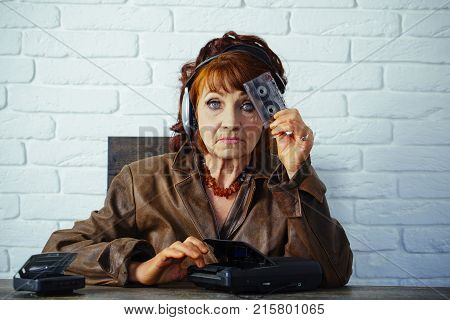 Audio book and new technology education. Old woman with cassette recorder listen music in headphones. Spy and operator. Old school music player radio. Granny dj in headset with cassette player.