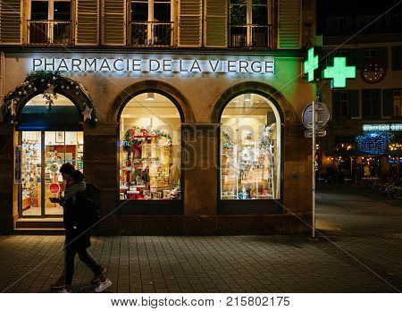 STRASBOURG FRANCE - NOV 21 2017: Pharmacie de la Vierge pharmacy neon sign on Christmas decorated facade in Strasbourg Alsace with silhouette of pedestrian walking by