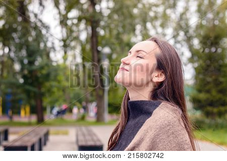 Portrait Of Young Beautiful Woman Doing Breath Of Fresh Autumn Air In A Green Park. The Concept Of P