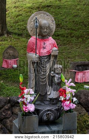 Nara - Japan, May 30, 2017: Traditional stone carved Jizo with red skirt honored and respected with flowers