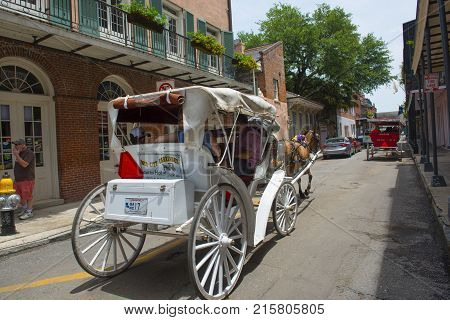 NEW ORLEANS - MAY. 29, 2017: Horse drawn carriage tours on Chartres Street between Dumaine Street and St Ann Street in French Quarter in New Orleans, Louisiana, USA.