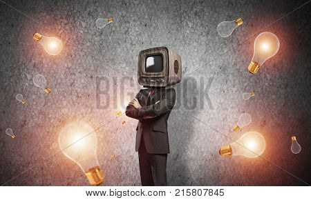 Businessman in suit with old TV instead of head keeping arms crossed while standing among flying lightbulbs and with gray dark wall on background.