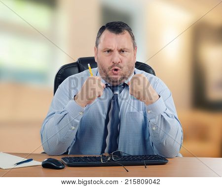 Angry man wearing blue shirt clenches his hands and combines lips a tubule. Middle-aged businessman sits at wooden office desk on indoors blurred background