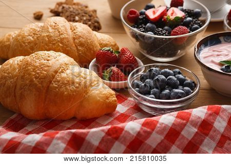 Rich continental breakfast. French crusty croissants, greek yogurt and lots of sweet berries for tasty morning meals. Delicious start of the day