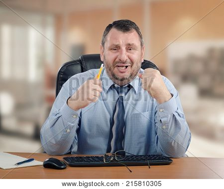 Panicked manager clenches his hands because he cannot make the right decision. Mature man wearing blue shirt and striped tie is ready to cry. He sits at wooden office desk
