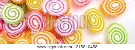 closeup of colorful candies on white background - Web banner with food concept