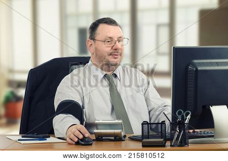 Middle-aged businessman learns to manage hypertension at workplace. He has just taken blood pressure and transmitting outcomes to telemedicine headquarters for consulting. Bearded man sitting at office desk looks at computer monitor
