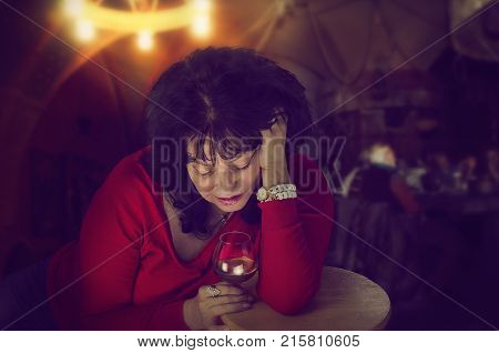 Alcoholic mature woman in red jumper drinks alone leaning on wooden stool in cafe. Black-haired woman is looking down into a glass of brandy sadly. Dark indoors blurred background