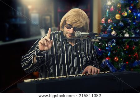 Old male singer in light yellow wig plays electric piano on Christmas Eve background