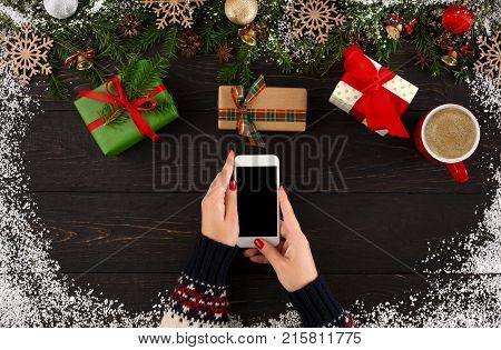 Christmas online shopping background. Close up of hands holding cell phone on rustic wooden table with Christmas gift boxes, coffee cup and garland frame. Internet commerce on winter holidays concept
