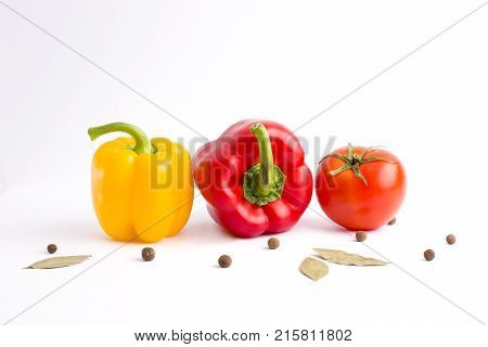 The red peppers and yellow peppers with tomatoes on a white background. Fresh vegetables on a white background. Composition from vegetables. Red and yellow peppers on a white background. Tomato with peppers on white background.