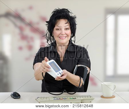Positive mature woman in black dress has just taken blood pressure and shows outcomes to camera. Smiling black haired woman looks after for herself therefore has normal blood pressure. She sits at white desk with grey keyboard on indoors blurred backgroun
