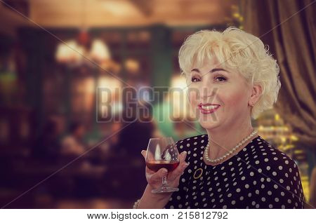 Mid-shot of short-cropped blonde hair mature woman wants to raise a toast with brandy. Happy cool-looking lady wearing polka dot jacket and pearl necklace stands on blurred interior background