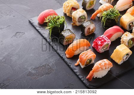 Sushi and rolls background, frame on black, top view. Colorful asian restaurant food set, traditional japanese cuisine