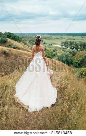 A Young Girl, The Bride In A Long Wedding Dress, Is Turned Her Back And Stares Into The Distance To