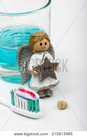 The tooth Fairy next to a tooth, toothbrush and mouth wash. The tooth fairy leaves Erin a reward in exchange for a tooth that has fallen out.