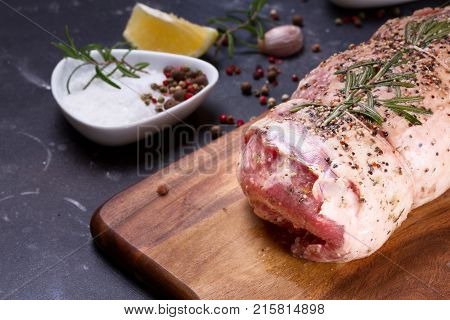 Raw lamb meat roll with spices on dark background