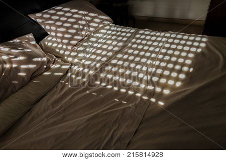 Unmade double bed with circle patterns from the closed shutter. Shows shade from the sun.