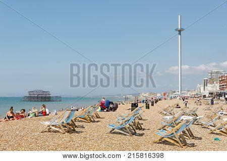 BRIGHTON GREAT BRITAIN - JUN 17 2017: Sunbathing people and deckchairs on the Brighton beach West pier in the background. June 17 2017 in Brighton Great Britain