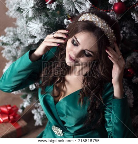 A Beautiful Girl With Long Hair In A Green Dress Near The Christmas Tree Adjusts The White Diade On