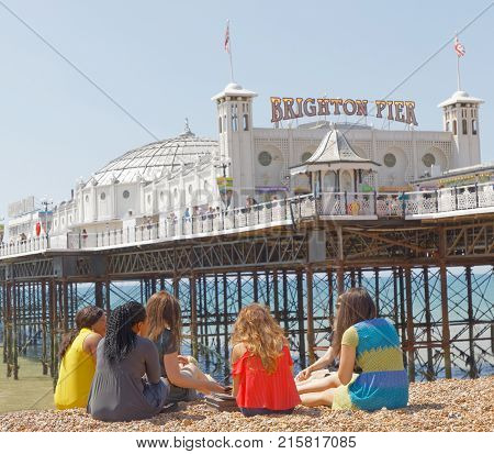 BRIGHTON GREAT BRITAIN - JUN 17 2017: Group of girls on a language course abroad sitting in front of Brighton pier. June 17 2017 in Brighton Great Britain