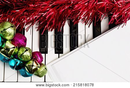 Christmas music concept. Blank paper on the piano with jingle bells and red tinsel.