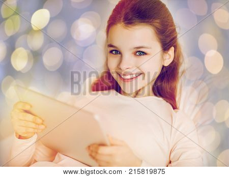 people, children and technology concept - happy smiling girl lying awake with tablet pc computer in bed over holidays lights background