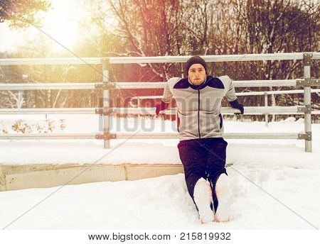 fitness, sport, people, exercising and healthy lifestyle concept - young man doing triceps dips and warming up at fence in winter