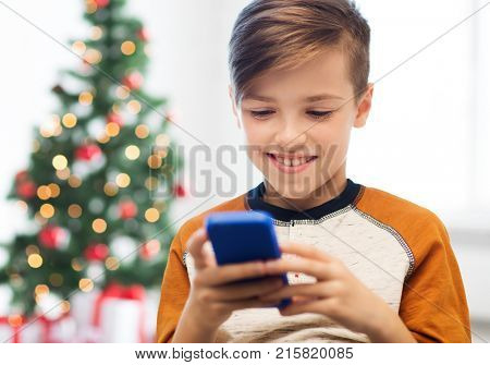 children, technology, communication and people concept - close up of smiling boy with smartphone texting message or playing game at home over christmas tree background