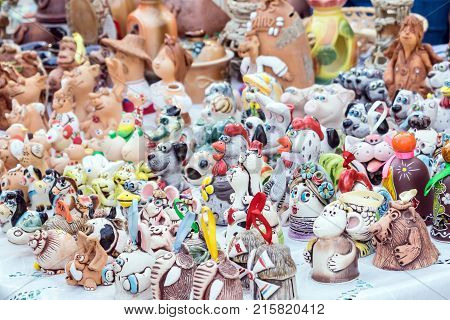 Colorful cute souvenir decorative clay bells wind chimes toys dolls figurines of animals and people. Handmade souvenir ceramic at the market traditional craft