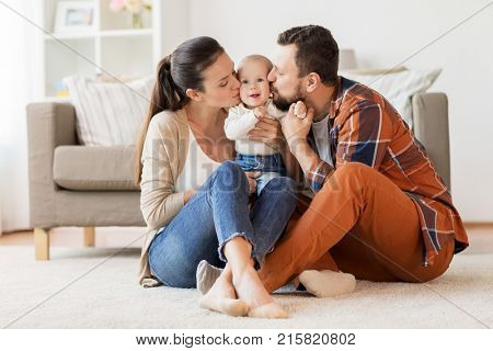 family, parenthood and people concept - happy mother and father kissing little baby at home
