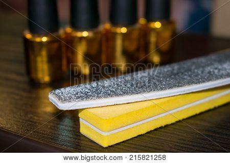 Buff and nail file on the background of bottles of nail polish. Two nail files emery boards
