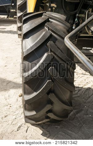 Close up of tractor tire selective focus. Tractor tire showing wheel entire and parts of tractor. Big tractor wheel with a ridge protector on sand