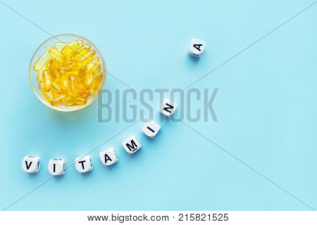 Yellow capsules in the round glass bowl and the word vitamin A from white cubes with letters on a blue background. healthy and medical concept. retinol retinal retinoic acid provitamin A carotenoid beta-carotene health benefits