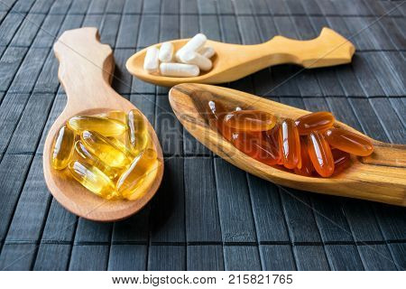 Nutritional supplements and vitamins for brain in three wooden spoons on a dark background. Variety of dietary supplements including gel capsules and Veggie Caps of Omega 3 Fish Oil lecithin ginkgo biloba. Selective focus