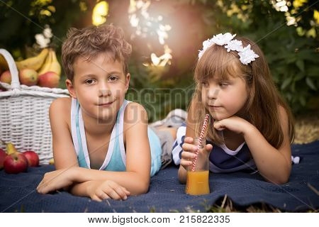 Happy Smiling Boy And Girl Lying Together On A Blanket And Having A Picnic