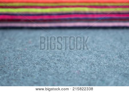 Pile of felt flaps blurred background. Defocus Stack of colorful felt flaps on a gray fabric background. Handmade creativity crafts sewing needlework background
