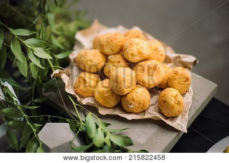 Bread balls stuffed with cheese. They are laid out on kraft paper. Beautiful concrete decor.