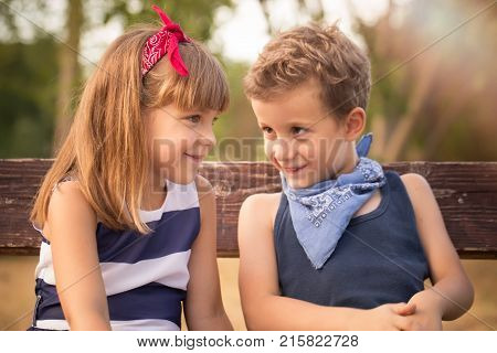 Little Sweet Boy And A Girl Sitting On A  Bench In The Park And Having Fun
