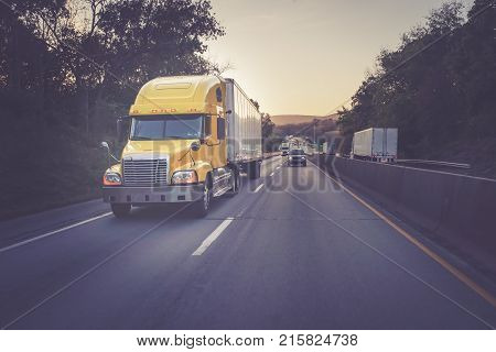 Yellow 18 wheeler semi trucks on highway road