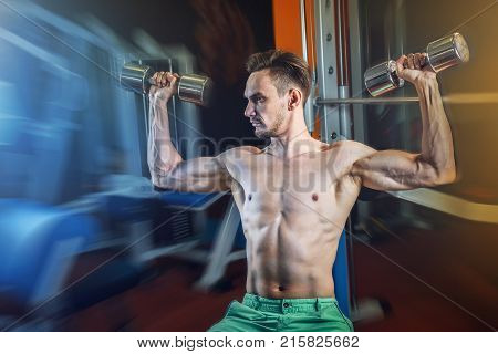 Handsome caucasian man working out at gym and doing shoulders exercises with dumbells