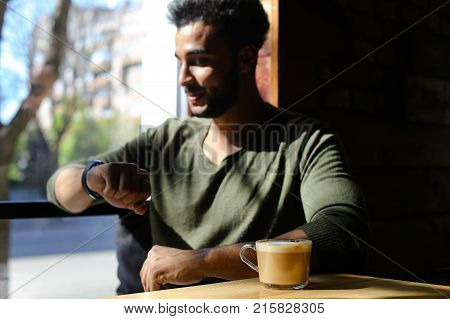 Arabian sits by table near cup of coffee and uses smart watch in caf . Happy boy has dimples, beard, full lips and black hair. Person dressed in khaki pullover. Concept of modern technologies and good atmosphere, places for resting.